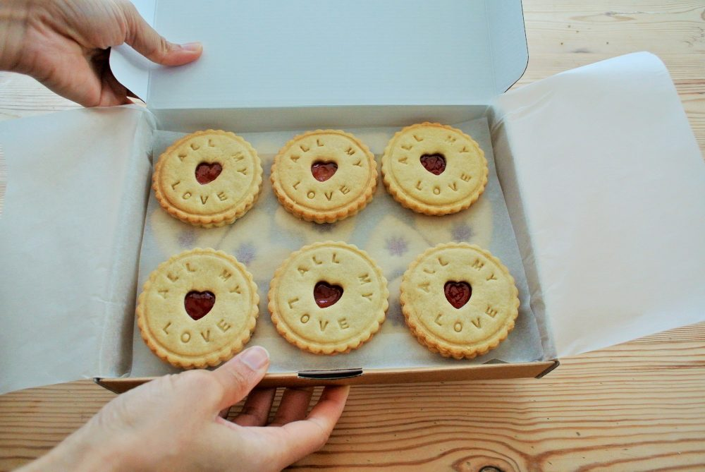 Bespoke biscuits in a large box held up for presentation